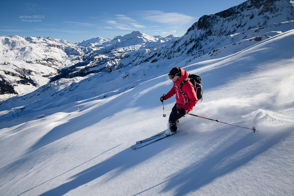 Skieur en descente dans la poudreuse dans la station d'Areches-Beaufort. Ciel bleu, neige fraiche. Massif du Beaufortin.