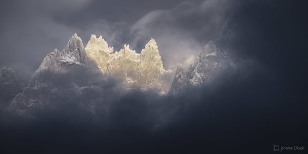 Les Aiguilles de Chamonix émergent des nuages en hiver sous la neige