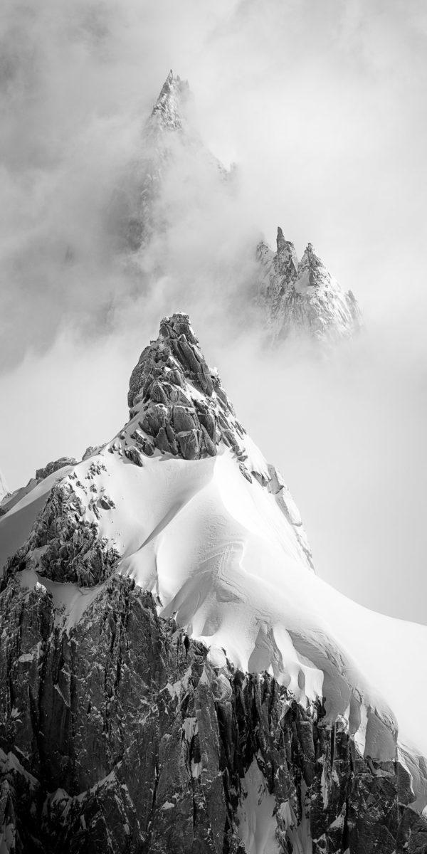 L'aiguille du Plan et au fond le Cardinal dans les nuages sous la neige. Massif du Mont Blanc.